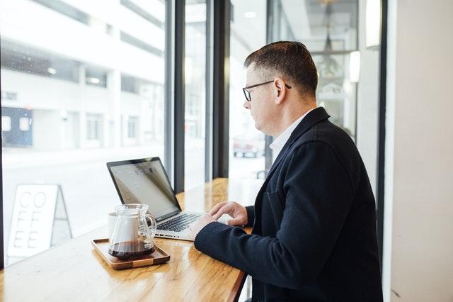 mężczyzna w garniturze pracujący na laptopie